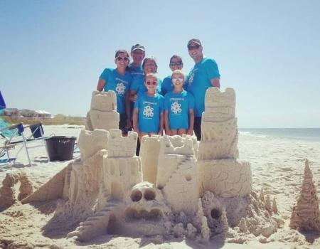 Sand castle and family on beach