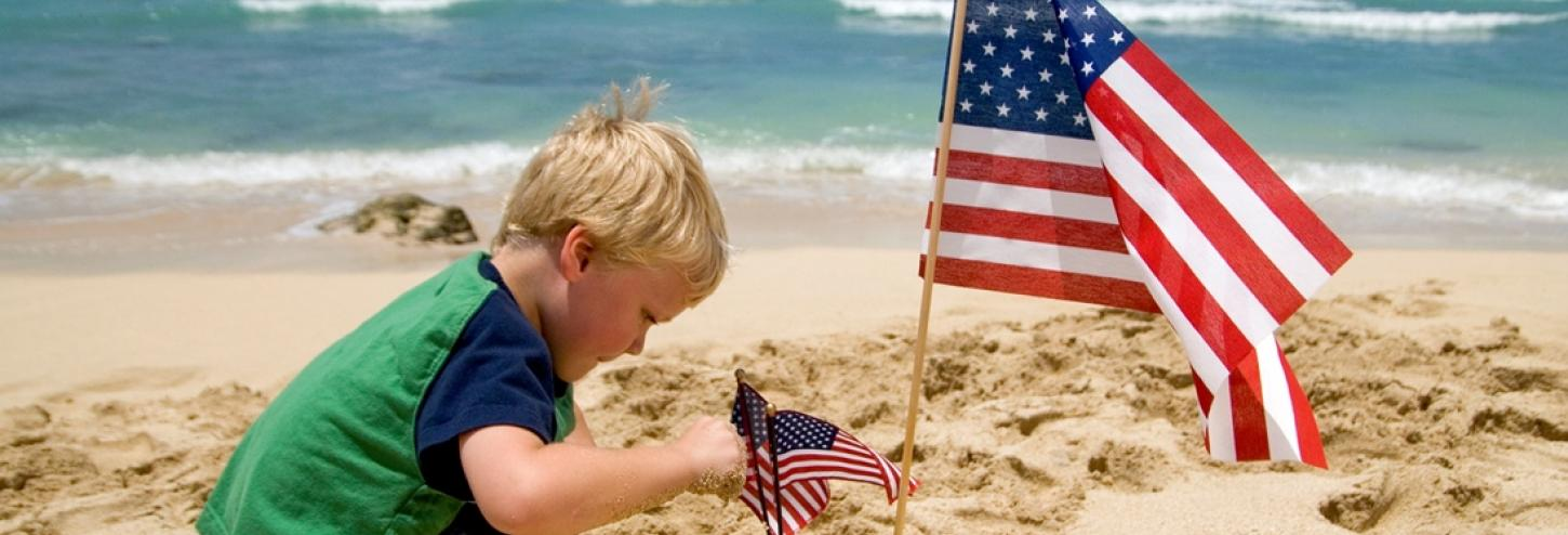Boy and American flag on the beach