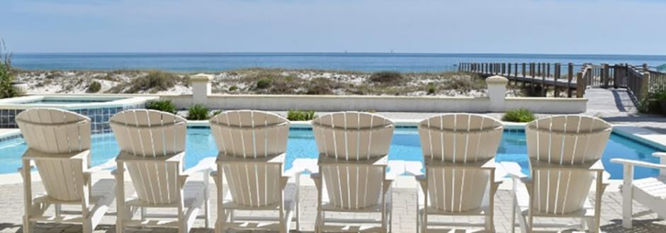 beach chairs in front of a pool
