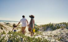A family walks to the beach in Gulf Shores, AL