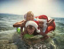 Kids at the beach in Santa hats