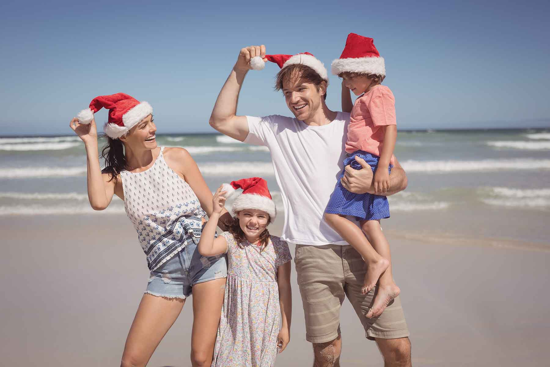 Family of four with Santa hats on the beach