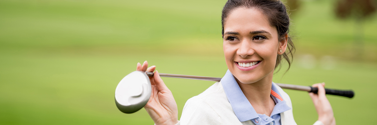 Woman holding golf club over shoulders