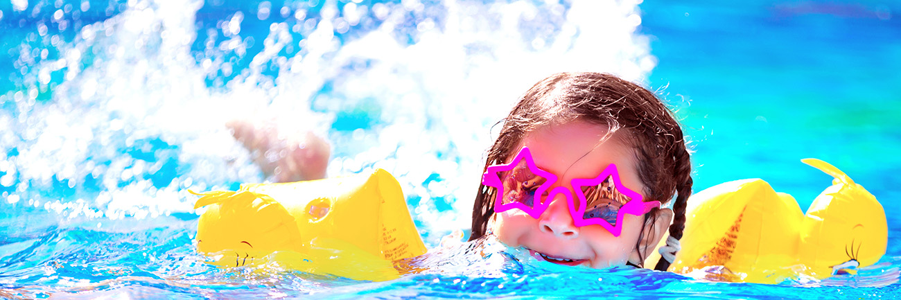 Young girl swimming in pool with floats and star shaped glasses