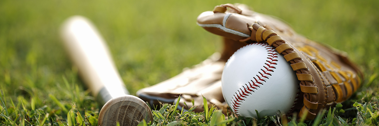 Baseball glove and ball laying in the field