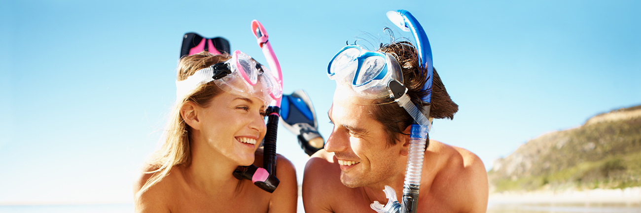 Couple with snorkel gear on smiling at eachother